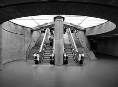 Below Stairs IV (Douguerreotype) Tags: monochrome circle underground concrete city bw uk metro escalator british england mono blackandwhite stairs subway britain gb london symmetry tunnel urban people steps tube