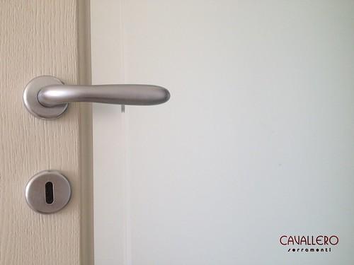 Dettaglio maniglia e vetro di una porta in Frassino