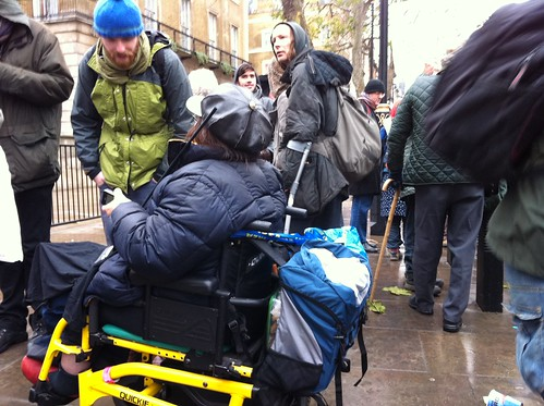 People milling around with a wheelchair user in focus in the foreground