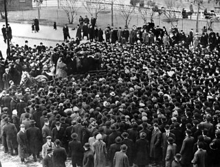 A crowd gathered around a man speaking from the back of a horse-drawn wagon