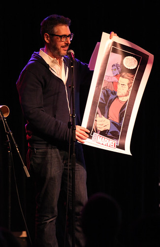 Ira Glass shows off the X-Men / This American Life poster, which he gave away to an audience member who told a holiday joke on stage.