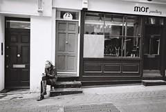 2010-1007-1326 (t-a-i) Tags: door uk england bw woman london girl mobile stair sitting fuji unitedkingdom iso400 soho coke carnabystreet fujifilm neopan ricoh gr1 gantonstreet  ricohgr1  neopan400cn fujincn400 fujicolorneopan400cn