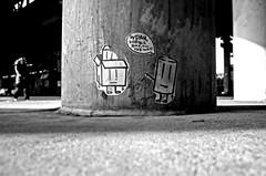 lil tiny fellers way down low (damonabnormal) Tags: street city urban blackandwhite bw streetart philadelphia canon concrete graffiti jan pavement stickers pillar january streetphotography urbanart pa labels philly graff thursday phl slaps urbanite 2011 citystickers alltheway philadelphiastreetart 40d philadelphiaurbanart