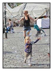 Bubbles Playing with a Child (Doyle Wesley Walls) Tags: lagniappe 0404 child bubbles woman female cutoffs fun joy streetphotography doylewesleywalls