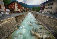 River through Zermatt, Switzerland (` Toshio ') Tags: toshio zermatt switzerland europe european mattervispa river village swissalps mountains water fujixe2 xe2 architecture cabins hotel riverbank rocks