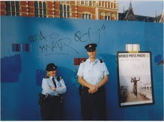 Amsterdam Police/World Press Photo (Khmanglo) Tags: street city blue people urban holland smile dutch amsterdam smiling graffiti garda uniform europe gun european cops dam police streetscene cop policewoman copper law centraalstation nederlands polizei coppers policeman fuzz centraal polis gendarme polizia worldpressphoto politie fiveo gendarmerie pulis polizie chrishondros worldpressphoto2004 poliz