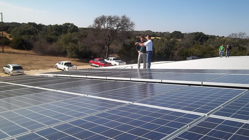 J. Tyler, Area Technician, USDA Rural Development in Hillsboro is shown inspecting the recently installed photovoltaic panels on the roof of the main building at Red Caboose Winery.