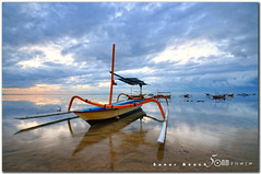 good morning - sanur beach bali (fiftymm99) Tags: morning travel blue sea bali holiday seascape reflection beach clouds umbrella sunrise bench indonesia landscape boat nikon asia traditional tourists suntan sands spa sanur sku d300 fiftymm99