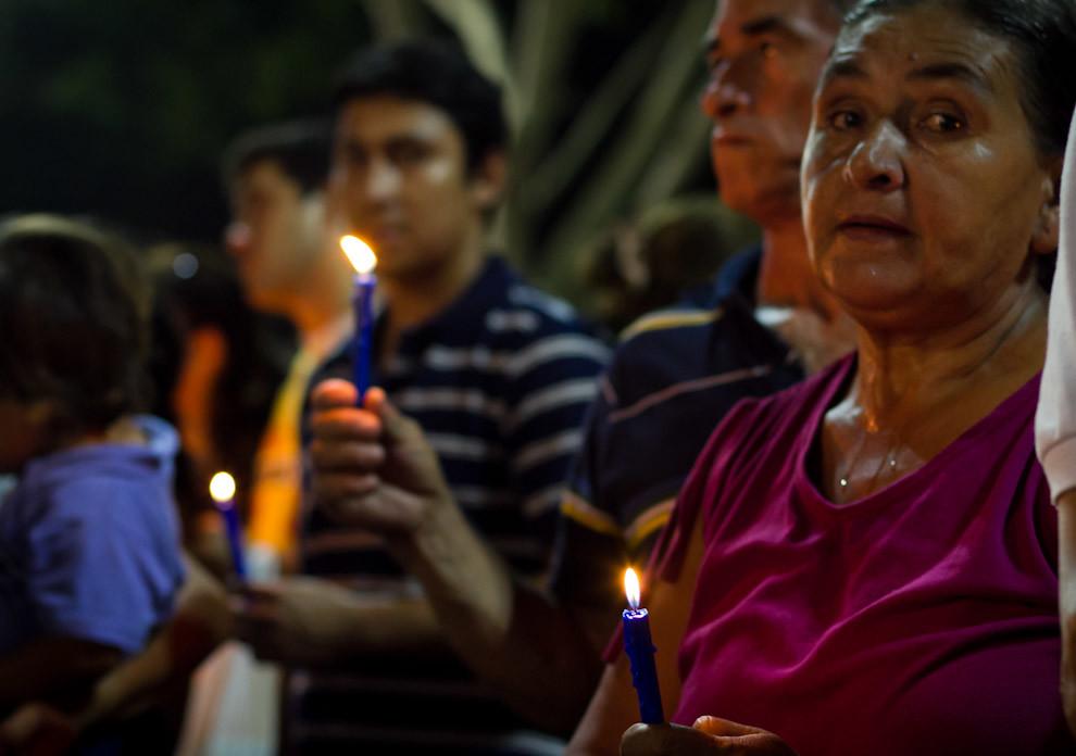 En medio del sofocante calor, las personas encendían sus velas y rezaban a la Virgen de Caacupé. (Tetsu Espósito - Caacupé - Paraguay)