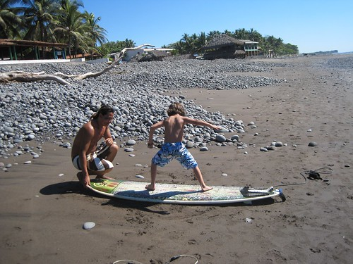 instructor teaching surf lesson to a kid in el tunco beach el salvador