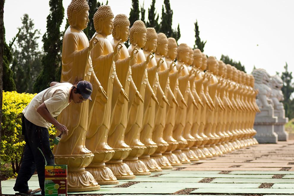 Un muchacho trabaja en el mantenimiento de las estatuas de un Templo Budista en Foz de Iguazú. (Elton Núñez - Foz de Iguazú, Brasil)