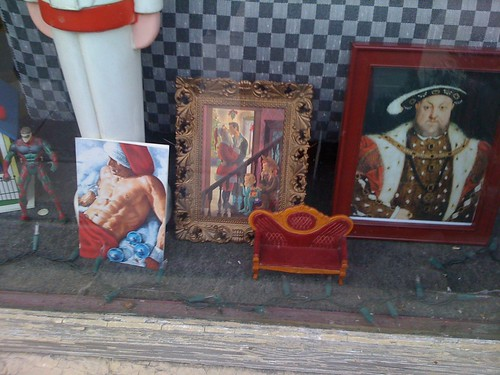 More decorations in the window: a Norman-Rockwell style picture showing two small children, one dressed inexplicably as a cowboy, peering through the banister of the stairs as a pyjama-clad fellow kisses a fellow dressed as Santa, under the mistletoe. Beside this is a small painting of very buff, shirtless guy reclining and wearing red trousers and a Santa hat. On the other side of the Rockwell-style picture is a portrait of Henry VIII. In the foreground is a small model of an upholstered chesterfield.