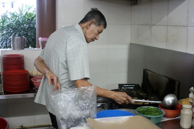 The old man takes his time to fry the Hokkien mee