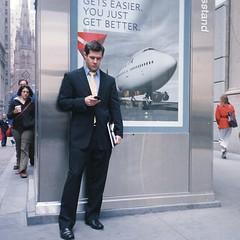 checking in (ho_hokus) Tags: nyc newyorkcity newyork businessman plane poster flying manhattan streetphotography delta email billboard financialdistrict business suit 35mmfilm advert trinitychurch wallstreet texting compactcamera olympusmjuii fuji160nps ny2010