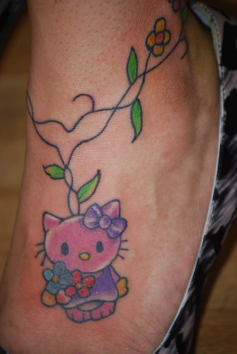 Tattoo of Hello Kitty with vines around ankle on foot tattooed by Cash