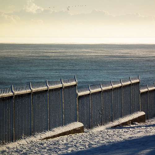snowy seafront fence