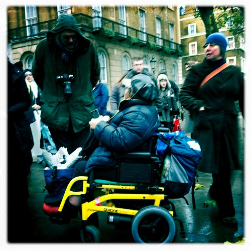 A man with a camera around his neck leaning forward to talk to a wheelchair user