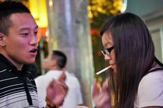 Health break (Roving I) Tags: china streets night longhair couples cigarettes sanya hainanisland lightingup healthrisks