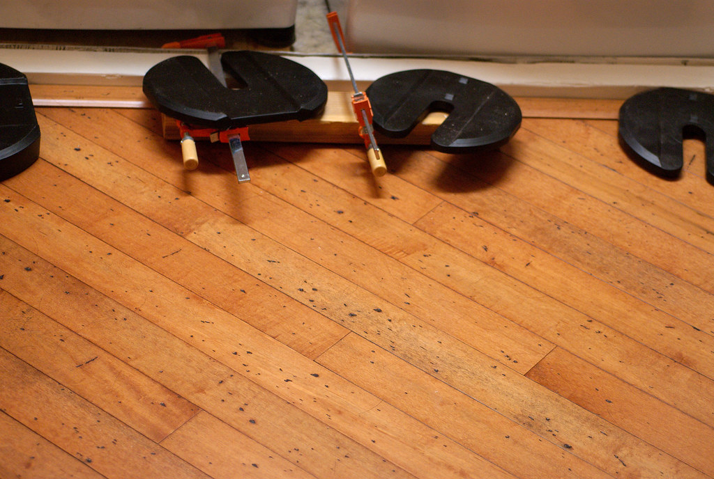 """A """"threshold"""" molding is used to separate the laundry closet's 2x4 (painted white) from the wood flooring."""