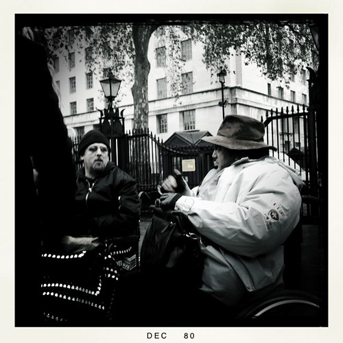 Black and white photo of 2 male wheelchair users conversing