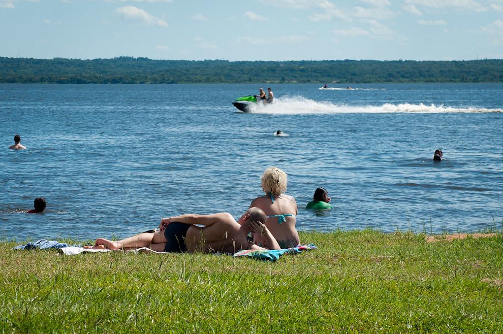 Tras la llegada del Verano 2011, el pueblo paraguayo se volcó a las ciudades más famosas por sus balnearios. Una pareja disfruta el sol en la playa del Lago Ypacaraí mientras otros se refrescan en el agua. El paseo en jetsky es otra habitual actividad en el lago mas importante de la Ciudad veraniega de San Bernardino. El lago Ypacaraí abarca aproximadamente 90 km² de superficie y sus dimensiones son 24 km de norte a sur y 5 a 6 km de este a oeste. Su profundidad media es de 3 metros. El paisaje que conforma el lago es muy bello, pues está rodeado por cerros con espesa vegetación y por tres pueblos que se extienden en las elevaciones circundantes.(Elton Núñez - Ypacaraí - Paraguay)