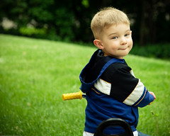 Toddler boy on tricylce smiling back at camera (Rebecca812) Tags: family blue boy portrait color cute male green smile yellow horizontal fun outside happy kid child play sweet tricycle blueeyes joy innocent son shy dimple jacket getty hood 3years oneperson blondhair canon5dmarkii familygetty2010 rebecca812 suckingonlowerlip