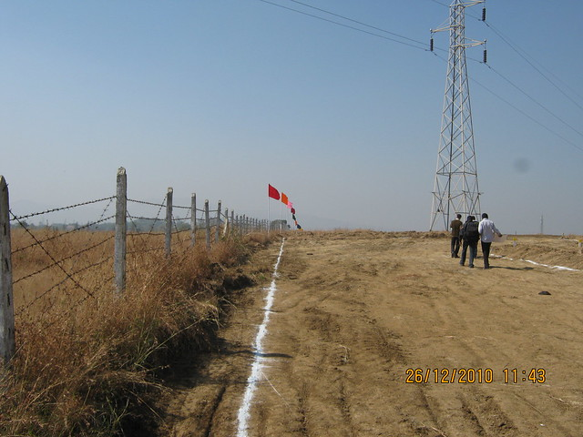 Fence and the High Tension Tower at Majestic  NA Bungalow Plots:  at Kanhe Phata - near Vadgaon - Talegaon, walking distance from Kanhe Railway Station, on Old Mumbai Pune Highway (NH 4)