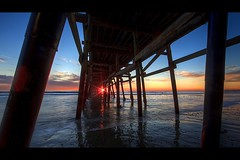 sunset through the pier (Eric 5D Mark III) Tags: ocean california light sunset sky usa cloud seascape reflection texture beach canon landscape pier twilight unitedstates wave structure sunburst orangecounty sanclemente backlighting ef14mmf28liiusm eos5dmarkii