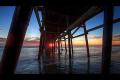 sunset through the pier (Eric 5D Mark III) Tags: ocean california light sunset sky usa cloud seascape reflection texture beach canon landscape pier twilight unitedstates wave structure sunburst orangecounty sanclemente backlighting ef14mmf28liiusm eos5dmarkii