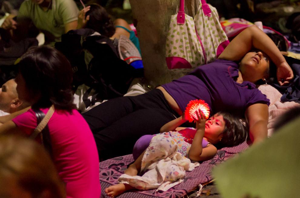 Esta niña se entretiene con un juguete, mientras su madre intenta descansar despues de una larga caminata para llegar hasta Caacupé. (Tetsu Espósito - Caacupé - Paraguay)