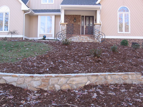 view of short stone retaining wall downhill from stone columns and steps on a home in southwest Raleigh, North Carolina