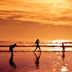 somewhere beyond the sea. (red.dahlia) Tags: ocean reflection silhouette night children waves cloudy oranges southerncalifornia santamonicabeach sunflare somewherebeyondthesea tarahelpedmechoosethepostedonesoifyoudontlikeitblameher kiddingimuchpreferthesquarecroptoo