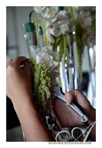 grace-ormonde-tabletop-mimosa-style- florish prepares green flowers to drape below white orchids for centerpiece and table arrangement for wedding style magazine- boston mass