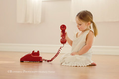 just a phone call away.... (Kimberly Chorney) Tags: playing vintage dress sweet littlegirl slip ponytails redretrophone naturallightvintage