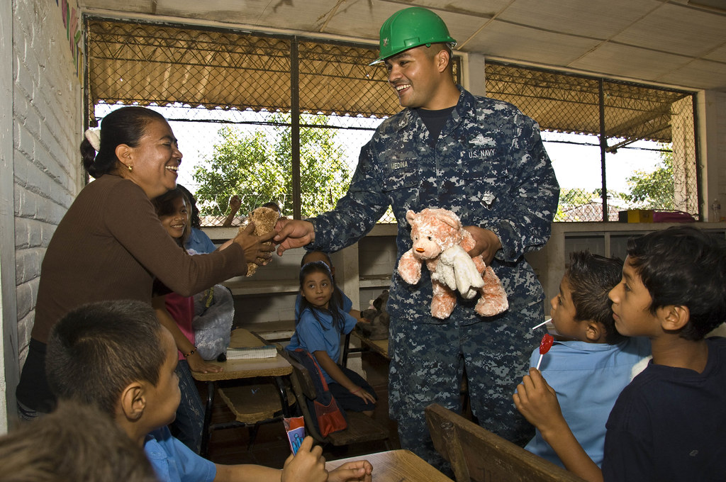 Navy corpsman gives toy to teacher in El Salvador.
