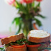 Two sandwhiches displayed in front of a vase of flowers.