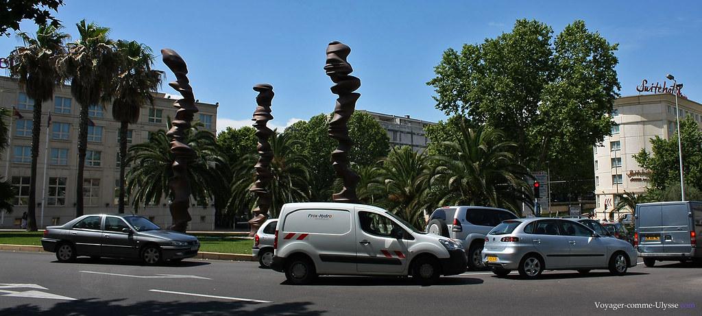 Sculptures modernes, palmiers et voitures