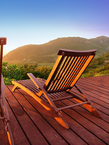 A wooden chair on a deck, looking into the sunset