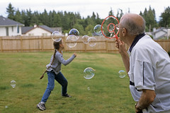 Grandfather and Granddaughter (Jim Corwin's PhotoStream) Tags: family playing man game male girl horizontal female standing fun outdoors photography concentration play families grandfather floating bubbles blowing running games run lass granddaughter relationship elderly enjoy bubble bond imagination youthful recreation generations activity generation carefree enjoyment bonding soapbubbles activities blowingbubbles childlike seniorcitizen bubblewand interacting bubblemaker relation casualclothes leisureactivity nevertooold everydayscene grandfatherly casualscene