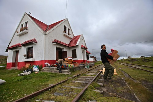 Rodrigo caries items to his house across the railroad tracks.