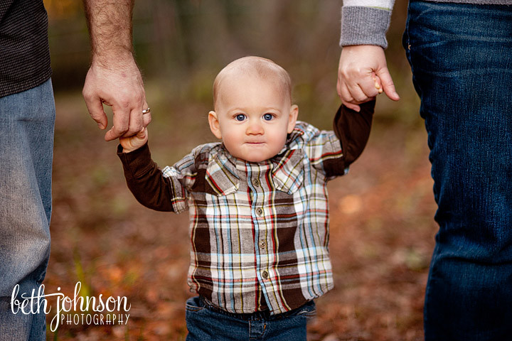 little boy on his first birthday with his parents holding his hands