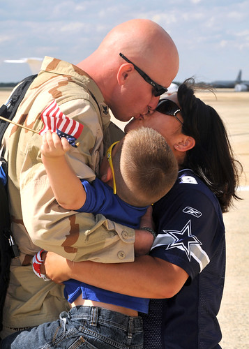 Sailor receives a hug and kiss from wife during homecoming.