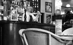 Cafe (Infinite Monkey) Tags: wood stella blackandwhite motion bar manchester cafe chair nikon slow bottles candid blurred motionblur slowshutter marketstreet wicker barman d90 nikon35mmf2 thechallengefactory
