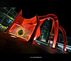 Red beast in the dark (iPh4n70M) Tags: wood light red sculpture paris france building statue architecture modern night contrast dark circle de rouge fire photography la photo chains nikon iron photographer photographie walk lumire towers structure bolas sombre photograph poi photowalk beast fuego nikkor bp fusion sparks tours nuit nocturne fury ballade feu parisian fer cercle dfense paille balade laine photographe parisienne immeubles parisien chanes nohdr limaille d700 1424mm