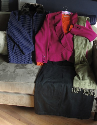 Photo of purple coat, fuchsia jacket, orange t-shirt, black skirt and olive green pashmina arranged on a couch as if people were wearing them. Kind of.