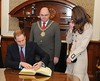 Prince William and Kate Middleton sign the visitors book during a visit to City Hall in Belfast on March 8, 2010.