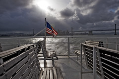 leaving on the ferry accross the bay (Bici Girl) Tags: bridge sky sunlight ferry clouds bay flag stormy