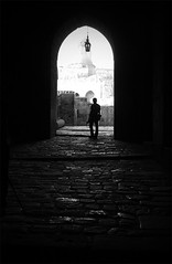 Photographer at the castle (gezimania) Tags: bw castle photographer citadel entrance doorway syria exit eskiehir kale aleppo halab oldquarter alep siyahbeyaz suriye halep kalegirii
