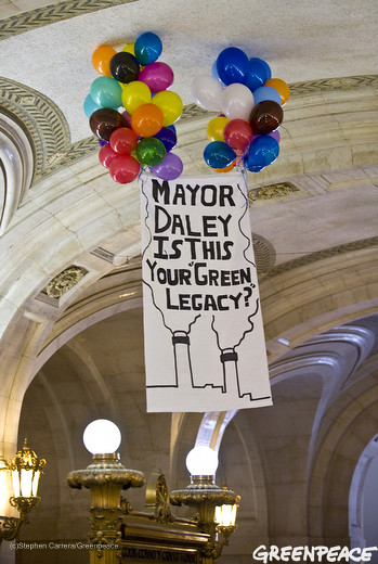 Environmental activists release a balloon banner in City Hall.