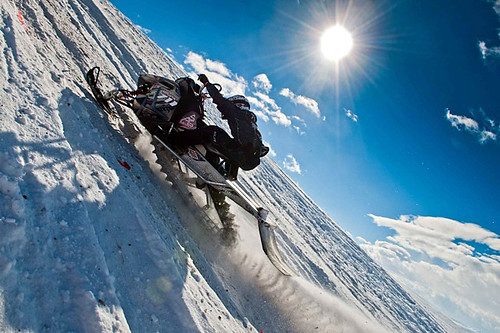 athlete climbing a mountain side on a snowmobile